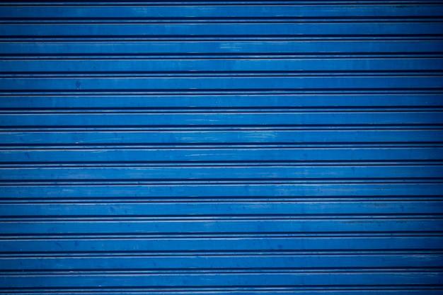 Oud blauw rolde metaaldeur op met luiken.