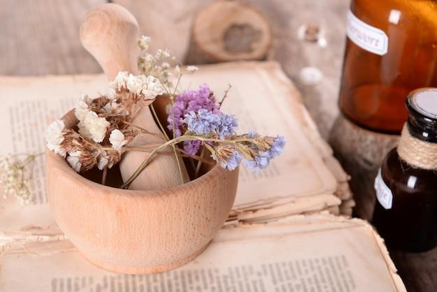 Oud boek met droge bloemen in mortel en flessen op tafel close-up