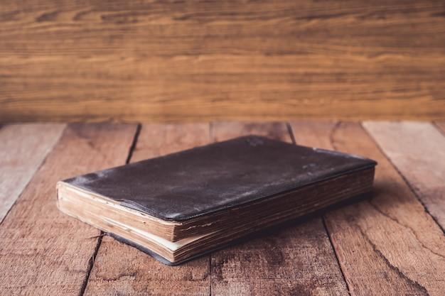 Oud boek met harde kaft op houten lijst.