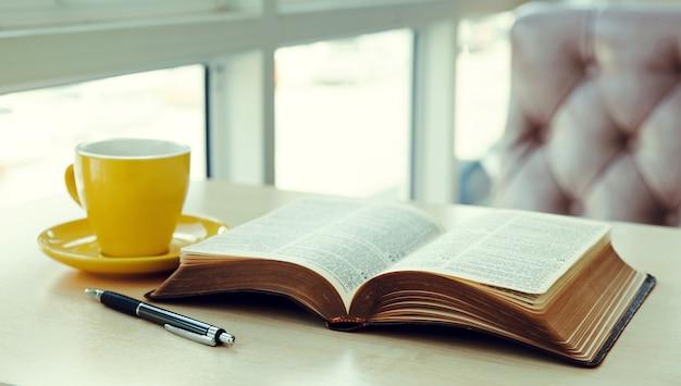 Oud boek openen met gele kop koffie op het bureau