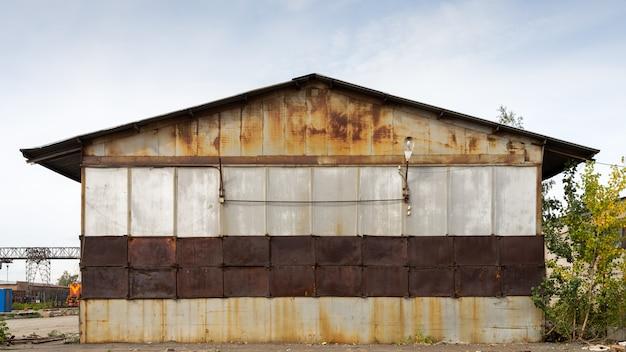 Oud bruin pakhuis met bladmetaalbekleding met straatlantaarns.