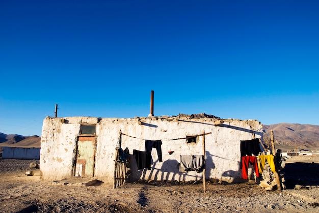 Oud doorstaan huis met bergketen op de achtergrond