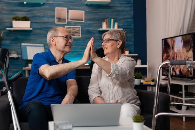 Oud echtpaar high five met behulp van laptopcomputer laptop