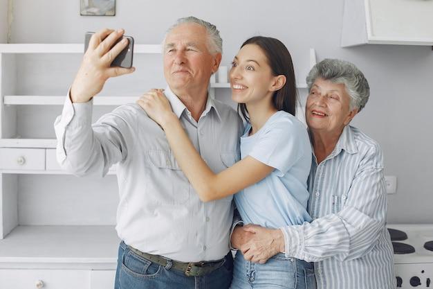 Oud echtpaar in een keuken met jonge kleindochter