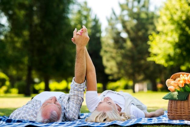 Oud echtpaar met opgeheven armen