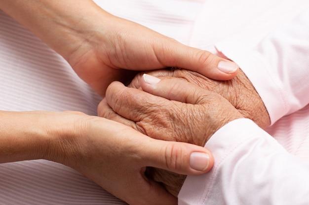 Oud en jong hand in hand op lichte achtergrond