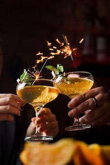 Oud en nieuw 2022 vieren met vuurwerk van sterretjes en cocktails drinken. munt met sinaasappelschijfje in een cocktailglas gevuld met alcoholcocktails.
