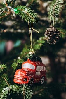 Oud en nieuw speelgoed: een hangende rode auto en rode ballen op een kerstboom met een onscherpe achtergrond