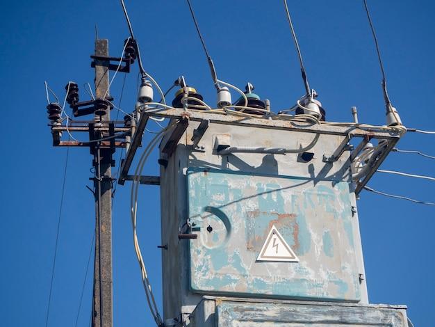 Oud en roestig transformatorstation in de zomer op een heldere dag tegen de blauwe hemel van dichtbij
