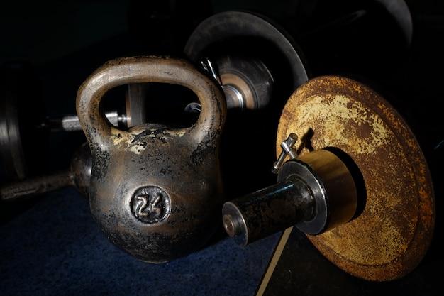 Oud en zwaar kettlebell-gewicht in donkere ruimte.