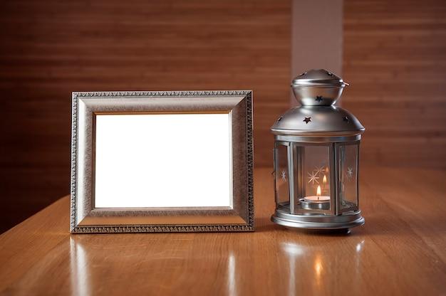 Oud fotoframe op de houten tafel tegen de achtergrond van een lantaarn