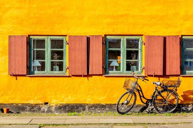 Oud geel huis van de wijk nyboder met een fiets in kopenhagen, denemarken.