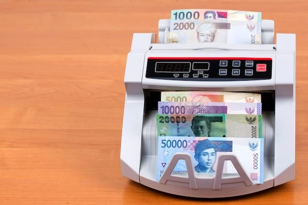 Oud geld uit indonesië in een telmachine