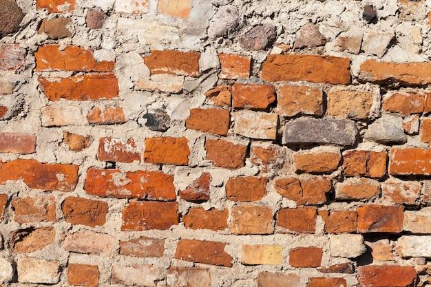Oud gerenoveerd bakstenen metselwerkmuurfort dat tijdens de oorlog is beschadigd