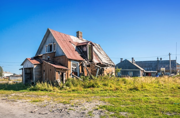Oud geruïneerd houten huis op de solovetsky-eilanden onder de blauwe herfsthemel