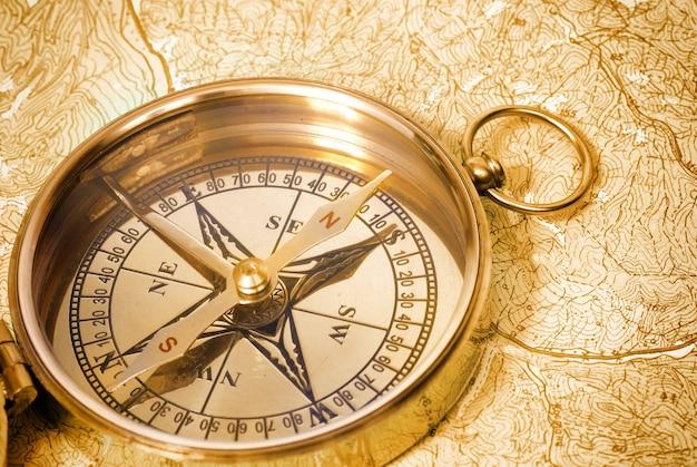 Oud gouden kompas op de oude kaart van grunge