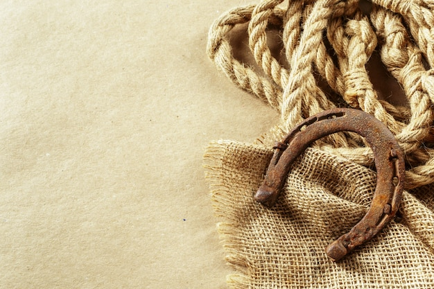 Oud hoefijzer en touw op houten planken