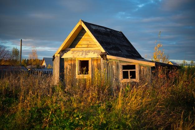 Oud houten dorpshuis dat met gras, oeral, augustus wordt overwoekerd