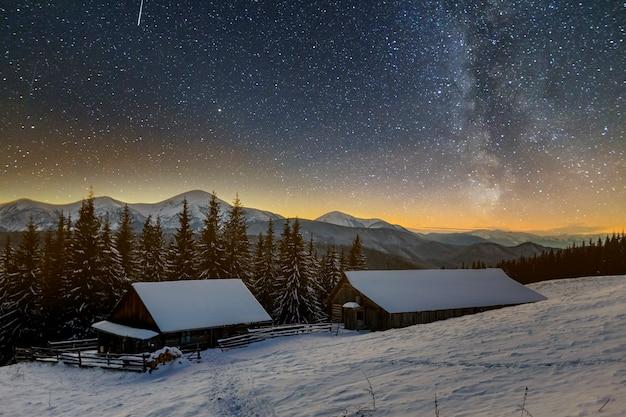 Oud houten huis, hut en schuur, stapel brandhout in diepe sneeuw op bergvallei, net bos, bosrijke heuvels op donkere sterrenhemel en melkweg. berg winter nacht landschap.