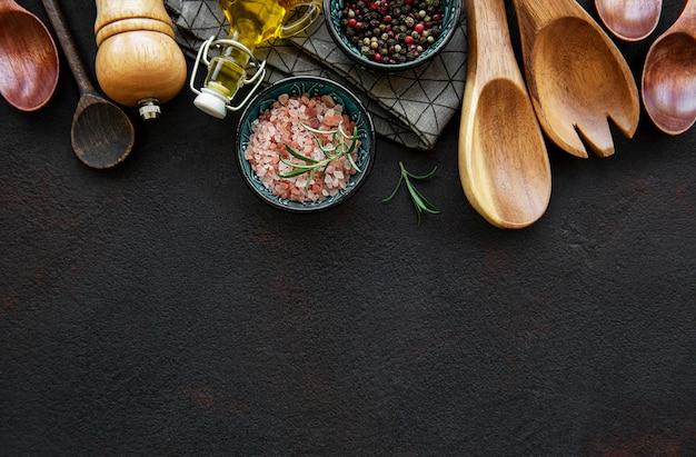 Oud houten keukengerei en kruiden als grens op een zwarte achtergrond