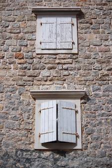 Oud houten raam met witte luiken van een mediterraan huis, vintage achtergrond