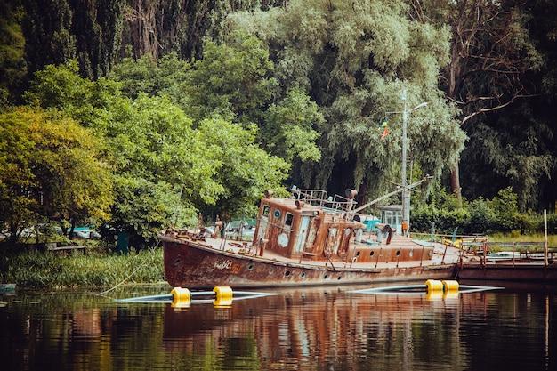 Oud houten schip dichtbij de oever van een meer, omgeven door weelderige natuur