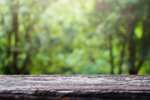 Oud houten tafelblad op groene vage abstracte achtergrond van gebladerteachtergrond. ready heeft ons producten voor display- of montageproducten gebruikt