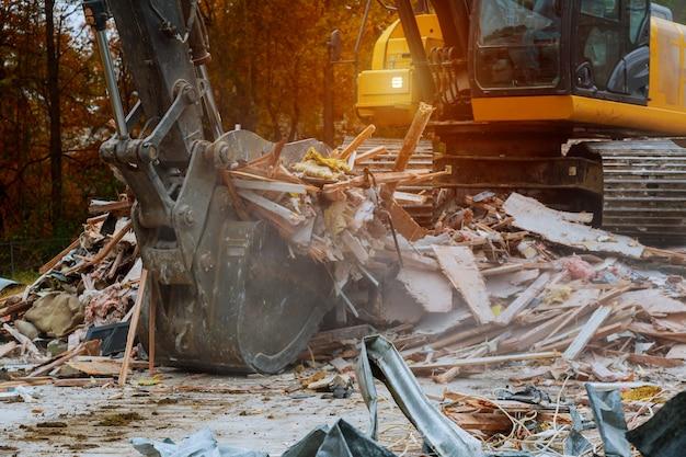 Oud huis dat door een grote backhoe wordt gesloopt