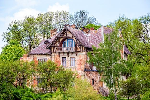 Oud huis in gotische stijl tussen groene bomen bij zonnig weer_