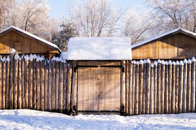 Oud huis in het siberische bos dat met palissadesneeuw wordt geschermd