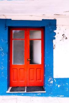 Oud huis met blauwe muur en rode deur