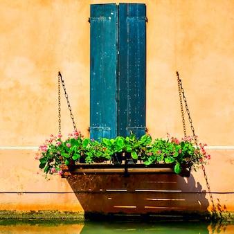 Oud huis met bloemen onder raam in treviso, veneto, italy