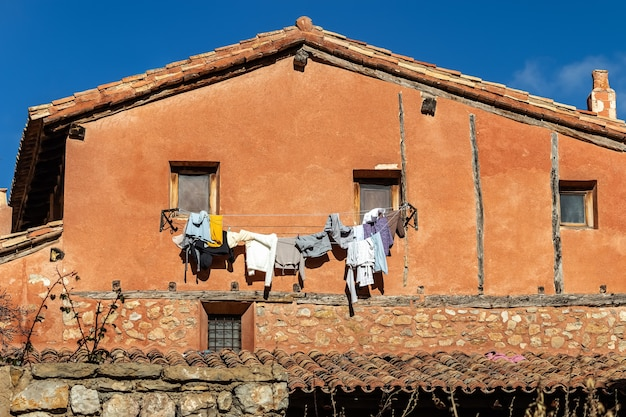 Oud huis met gewassen kleren die aan touwen hangen die aan de vensters hangen. albarracin spanje.