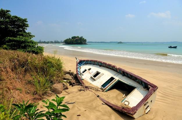 Oud jacht gestrand op een strand na stormen in de oceaan