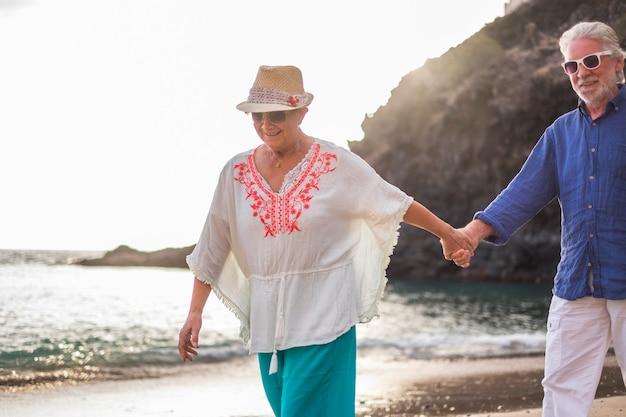 Oud kaukasisch paar mooie man en vrouw wit haar en hoed lopen samen op het strand genietend van het nieuwe gepensioneerde volwassen leven derde leeftijd met vrijheid van werk en kantoren