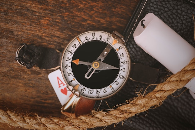 Oud kompas met touw, kaars en kaart op vintage hout