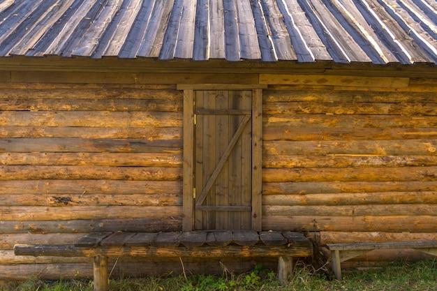 Oud landhuis gemaakt van boomstammen. bankje thuis