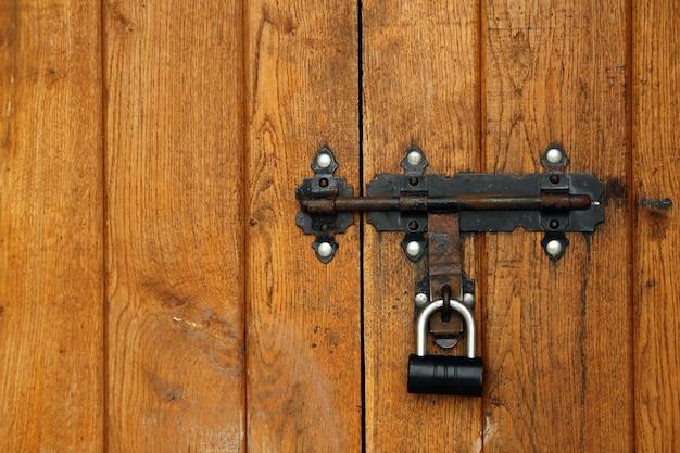 Oud metaalslot op de houten deurachtergrond