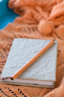 Oud notitieboekje voor verslagen, bal die van garen op houten oranje gebreide plaid liggen