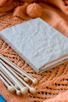 Oud notitieboekje voor verslagen, bal van garen en breinaalden die op houten oranje gebreide plaid liggen