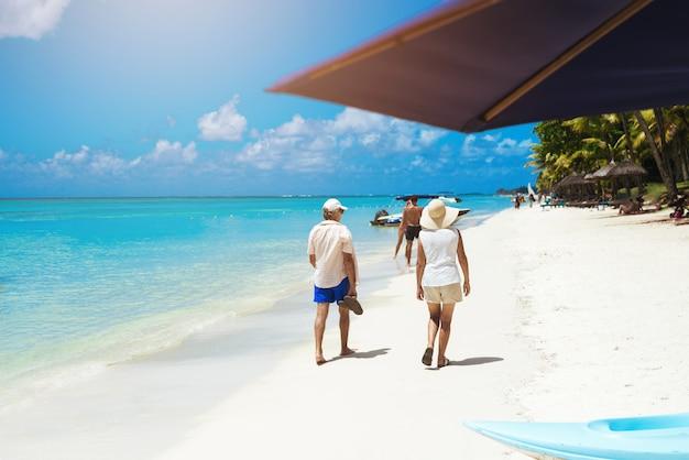 Oud paar dat door oceaankust loopt die van verbazend tropisch uitzicht geniet
