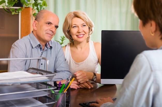 Oud paar gepensioneerden praten met werknemer