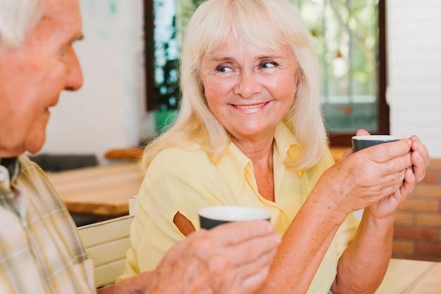 Oud paar het drinken thee op openluchtterras