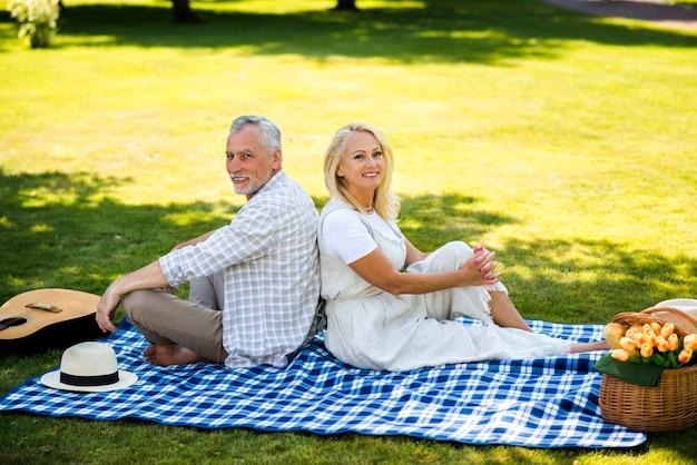Oud paar op een deken die de camera bekijkt