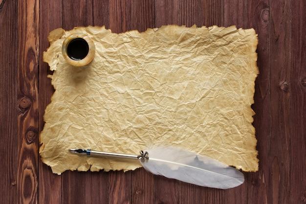 Oud papier en inkstand met een ganzenveer op een houten achtergrond