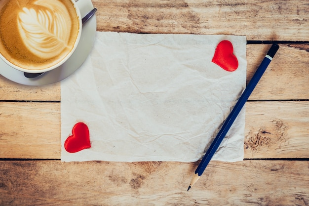 Oud papier en rood hart, koffiekopje met potlood op houten achtergrond voor een wenskaart van de valentijnskaart.