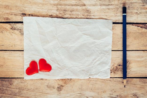 Oud papier en rood hart met potlood op houten achtergrond voor valentijn wenskaart.