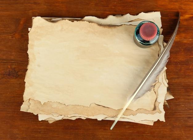 Oud papier, inkt en veren op houten tafel