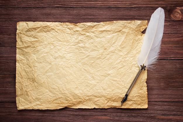 Oud papier op bruin houtstructuur met witte veer