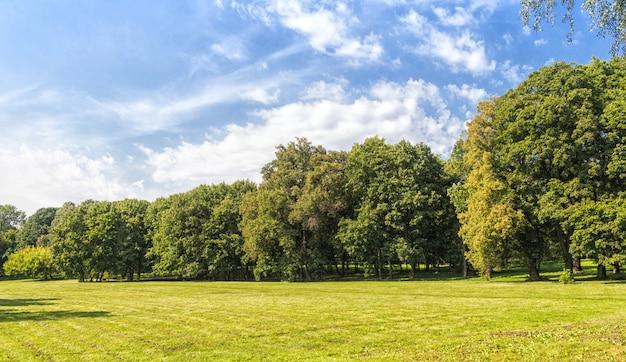 Oud park met groene gazons en grote bomen.